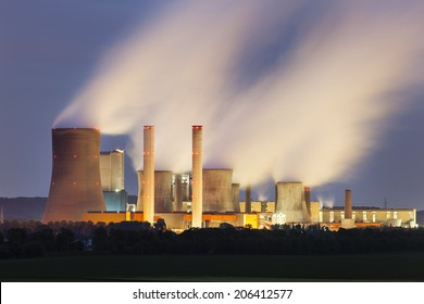 A coal-fired power station in the distance at night. The power station Niederaussem has the second highest cooling tower in the world with a height of 200m.