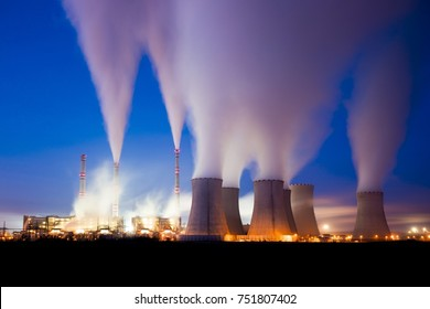 A coal-fired power station in the distance at night. Pocerady, Czech republic