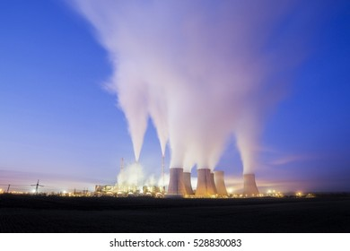 coal-fired power station in the distance at sunrise. Pocerady, Czech republic