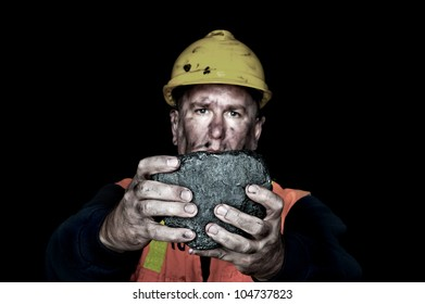 A coalminer holds out a large chunk of energy rich coal in a dark coalmine.