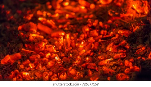 Coals, red hot, smoldering in the oven, shallow depth of field, background.
