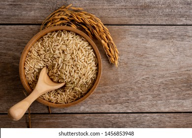 Coarse brown jasmine rice ( milled rice imperfectly cleaned,unpolished or half milled rice) in wooden bowl and paddy isolated on old rustic wood background. Healthy food and diet concept.Top view.