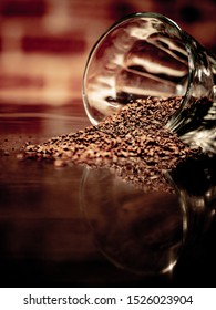 Coarse coffee grind scattered out of a glass