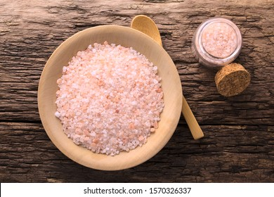 Coarse pink Himalayan salt on wooden plate, wooden spoon and small glass bottle of salt on the side, photographed overhead