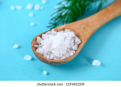 Coarse salt crystals on a blue table. Wooden spoon with sea salt. Background for advertising salt. Table salty. Salted food.
