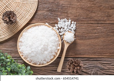 Coarse Sea salt on wooden plate and spoon on wood background. Top view and Copy space.