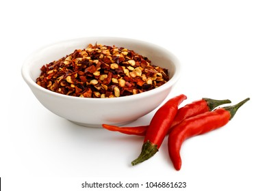 Coarsely ground chilli peppers in white ceramic bowl isolated on white. Fresh chillies.