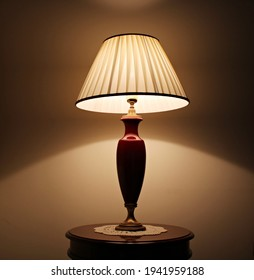Coassic elegant lamp with illuminated lampshade on a small round table in the room.
