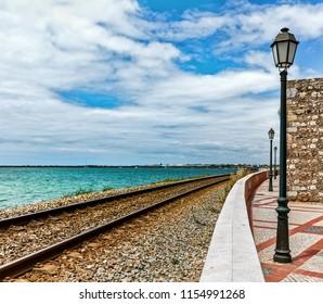Coast of Atlantic Ocean in the city of Faro, Portugal. Summer sunny day. Railway.