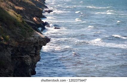 Coast of the Azov Sea, Crimea. Rocks and waves of the sea.