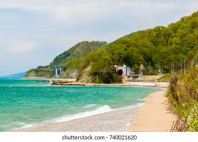 The coast of the Black Sea with mountains and railway tunnel in sunny summer day, Sochi, Russia