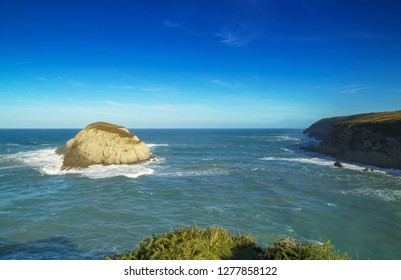 Coast of Cantabria, December, small island by Playa de Covachos beach, sandbank covered by water, big waves breaking