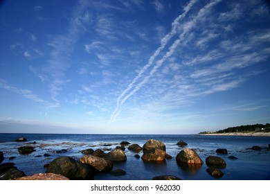 coast in denmark a sunny summer day, blue sky and rocks in the water