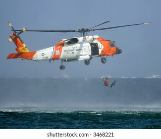 Coast Guard helicopter rescuing man from ocean.