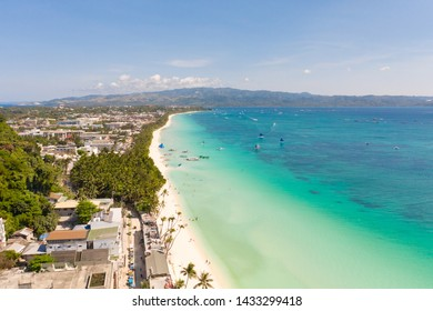 The coast of the island of Boracay. White beach and clear sea. Seascape with a beautiful coast in sunny weather. Residential neighborhoods and hotels on the island of Boracay, Philippines, view from