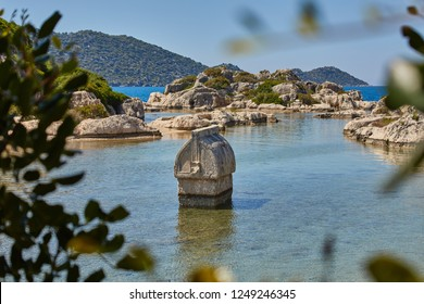 Coast of the island in the Mediterranean sea, picturesque with the ruins of ancient Lycian towns and tombs-sarcophagi of Aperlai, Simena Teimussa Dolihiste. Kekova, Turkey