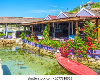 The coast of Kalekoy village at Kekova bay is occupied with cozy rustic cafes and beautiful restaurants, decorated with flowers and plants in pots, Turkey.