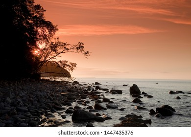 Coast line of island Ruegen at sunset with orange sky and siluhettes of rocks in the water