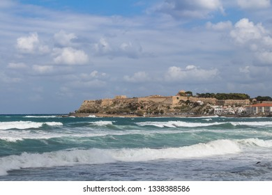 Coast of the Mediterranean sea with foamy waves. Venetian fortress in the background. Cloudy autumn sky. Horizon of the sea. Rethymno, Crete, Greece.