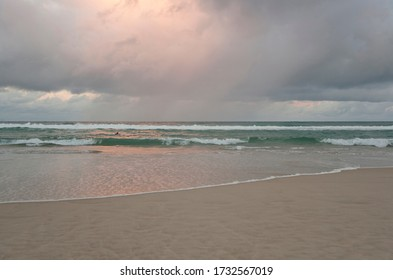 Coast on the East coast of Australia, Sunshine Gold coast, evening deserted beach. Wet sand and pink gray clouds.