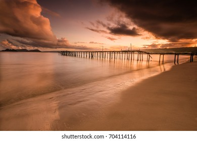 Coast of Pacific Ocean in Cambodia with old wooden pier on background. Golden hour moody sunset and dramatic clouds.