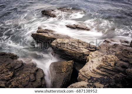 Coast with rocks and water. Silk water in a coast of Spain. Waves and rocks. Horizontal Composition