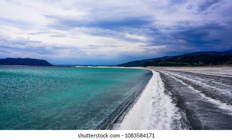 The coast of Salt Lake (Tuz Golu), Turkey. The breathtaking lake landscape under cloudy sky. White sand and amazing blue unique lake on a cloudy day. Bad weather. Laptop wallpaper image. Lake in Asia.