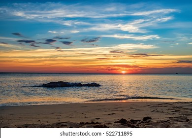 Coast of the sea at colorful sunset, Koh Chang, Thailand. Beach sunset is a golden sunset sky with a wave rolling to shore as the sun sets over the ocean horizon