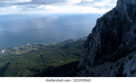 The coast of the sea with a small town near green forest, aerial view from the mountain. Shot. Wonderful seascape and high rocks with green trees on cloudy sky background in a summer sunny day.