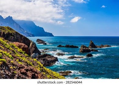 Coast or shore of Atlantic ocean with green mountain or rock and blue sky with clouds and skyline or horizon in Tenerife Canary island, Spain at spring or summer
