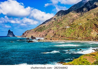 Coast or shore of Atlantic ocean with green mountain or rock and blue sky with clouds and skyline in Tenerife Canary island, Spain at spring or summer