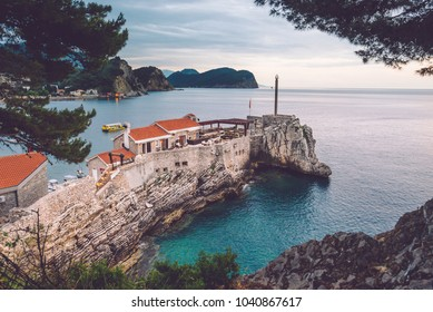 Coast venetian fortress Castello in Petrovac village, Montenegro. Montenegrin landscape with popular tourist attraction in Petrovac and Adriatic sea by evening golden hour.