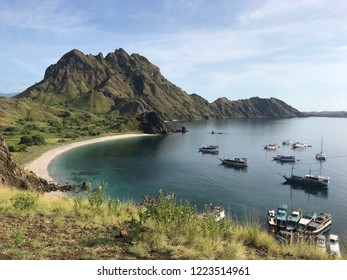Coast view of Padar Island with dark blue water surface and tourist boats surrounding by the hills in Komodo National Park Labuan Bajo, Flores, Indonesia