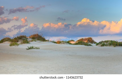 Coastal background of sandy beach with dunes beneath a cloud-filled blue sky on the Outer Banks of North Carolina.