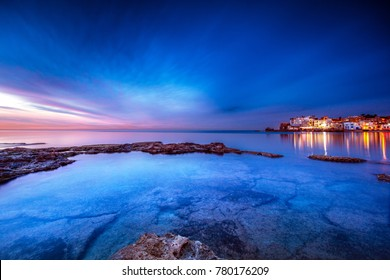 Coastal city on sunset, view on Batroun and mediterranean sea, glowing lights from the houses at night, Batroun is a coastal city in northern Lebanon and one of the oldest cities in the world