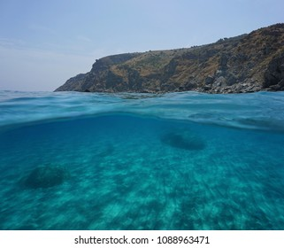 Coastal cliff and sand underwater, split view above and below water surface, Mediterranean sea, Marine reserve of Cerbere Banyuls, Pyrenees Orientales, France