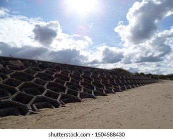 Coastal defences at beach with sun in background