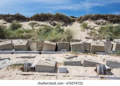 Coastal erosion management with concrete blocks. Sea defenses in front of vulnerable beach cliff face.