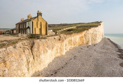 Coastal erosion, Sussex, England. A diminishing row of terraced houses displaying the effects of coastal erosion on the chalk cliffs of the south of England.