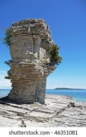 Coastal flowerpot rock formation with island