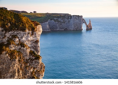 coastal landscape along the Falaise d'Aval the famous white cliffs of Etretat village with the Porte d'Aval natural arch and the rock known as the Aiguille d'Etretat