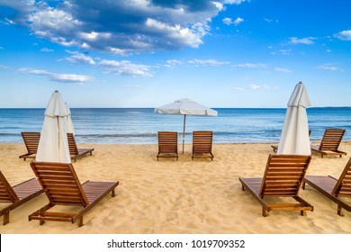 Coastal landscape - Beach umbrellas and loungers on the sandy seashore, the Kavatsi bay near city of Sozopol in Bulgaria