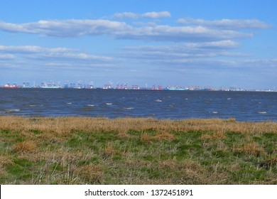 Coastal landscape of the North Sea: Salt marshes in the front, Wadden Sea at high tide, the port facilities of the city Bremerhaven in background - near the village Butjadingen, Lower Saxony, Germany.