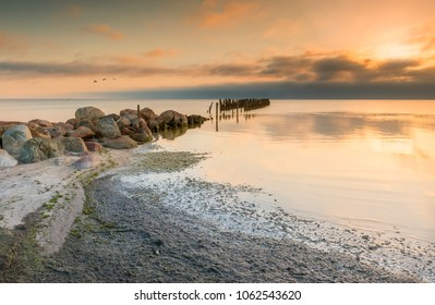 Coastal landscape with old broken pier, Baltic Sea. Colorful sunrise near a village of fishermen, where traditional fisheries was flourished in 20-th century, Baltic Sea