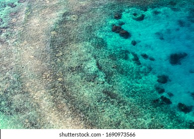 Coastal landscape of Persian Gulf, rocky seabed is under blue shallow water. Natural photo. Bird eye view
