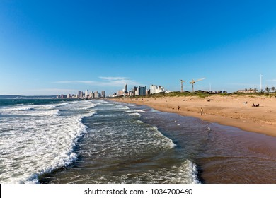 Coastal landscape of waves breaking on beach against blue city skyline in Durban, South Africa
