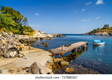 Coastal landscape - the wooden pier and boats in rocky bay, near city of Sozopol on the Black Sea coast in Bulgaria