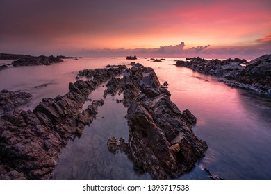 Coastal long exposure shot of a colourful sunrise at rocky beach formation in Chendering, Terengganu, Malaysia.