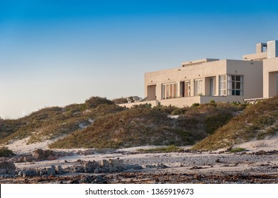 Coastal properties in Port Nolloth, South Africa. Sunset with blue sky, light clowds, rocks, ocean and sand dunes.
