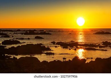 Coastal rocks of Casteneira beach in San Vicente of O Grove at golden sunset